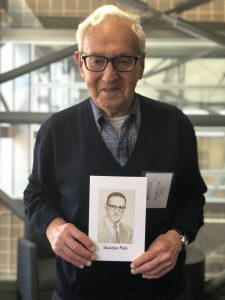 Sheldon Fink '54 holds his class exit photo