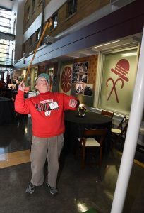 Alumnus throws cane over cane toss display